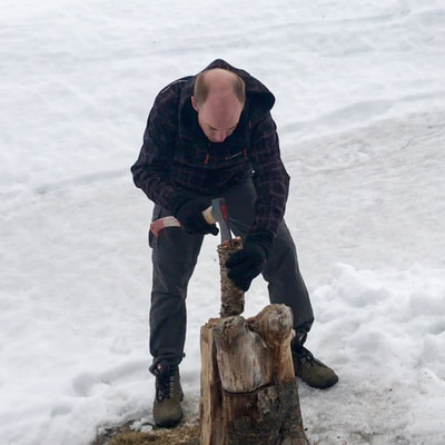 chopping wood in the snow in arctic Norway